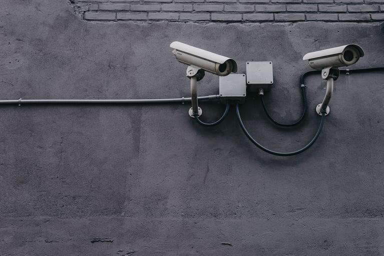 Deux caméras sur mur gris