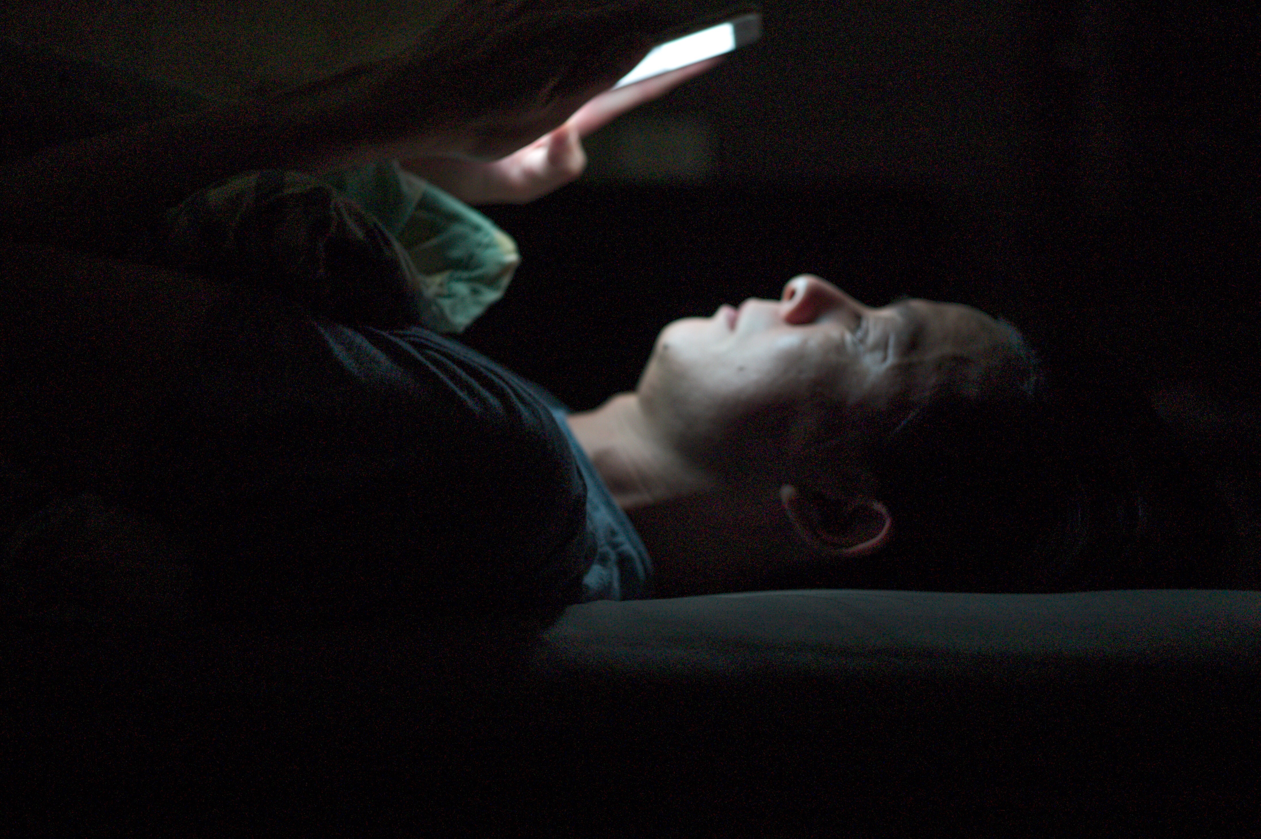 A man's face lighted by a smartphone in a dark room