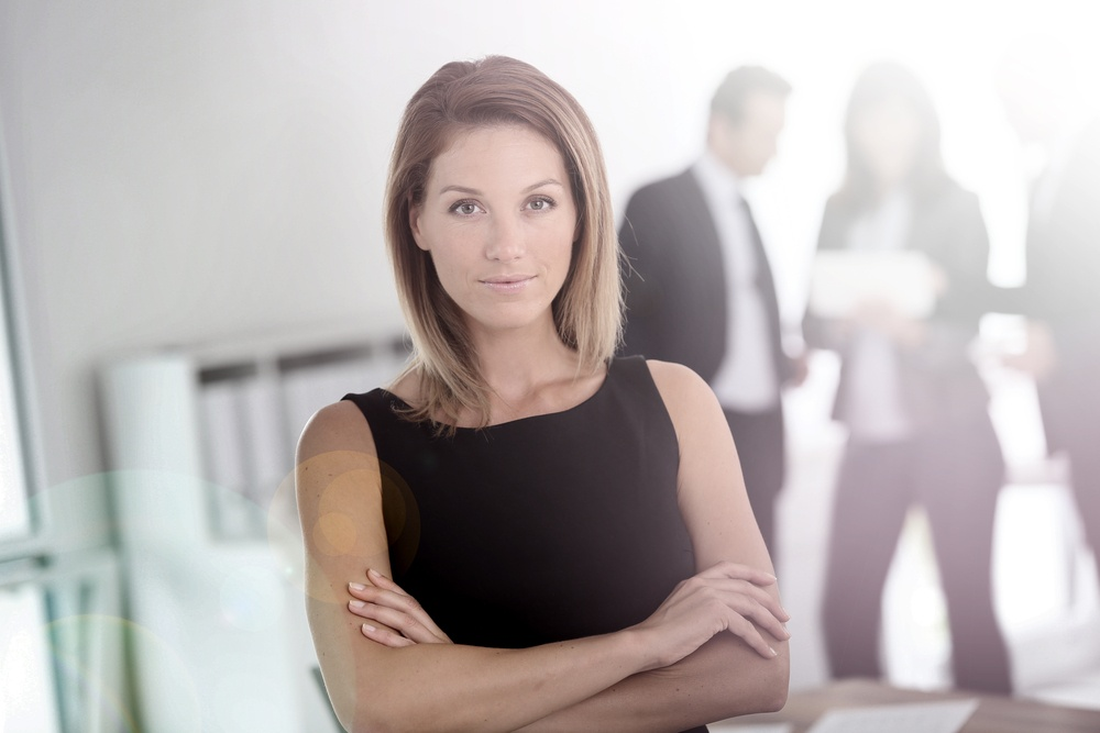 Portrait of attractive businesswoman, people in background