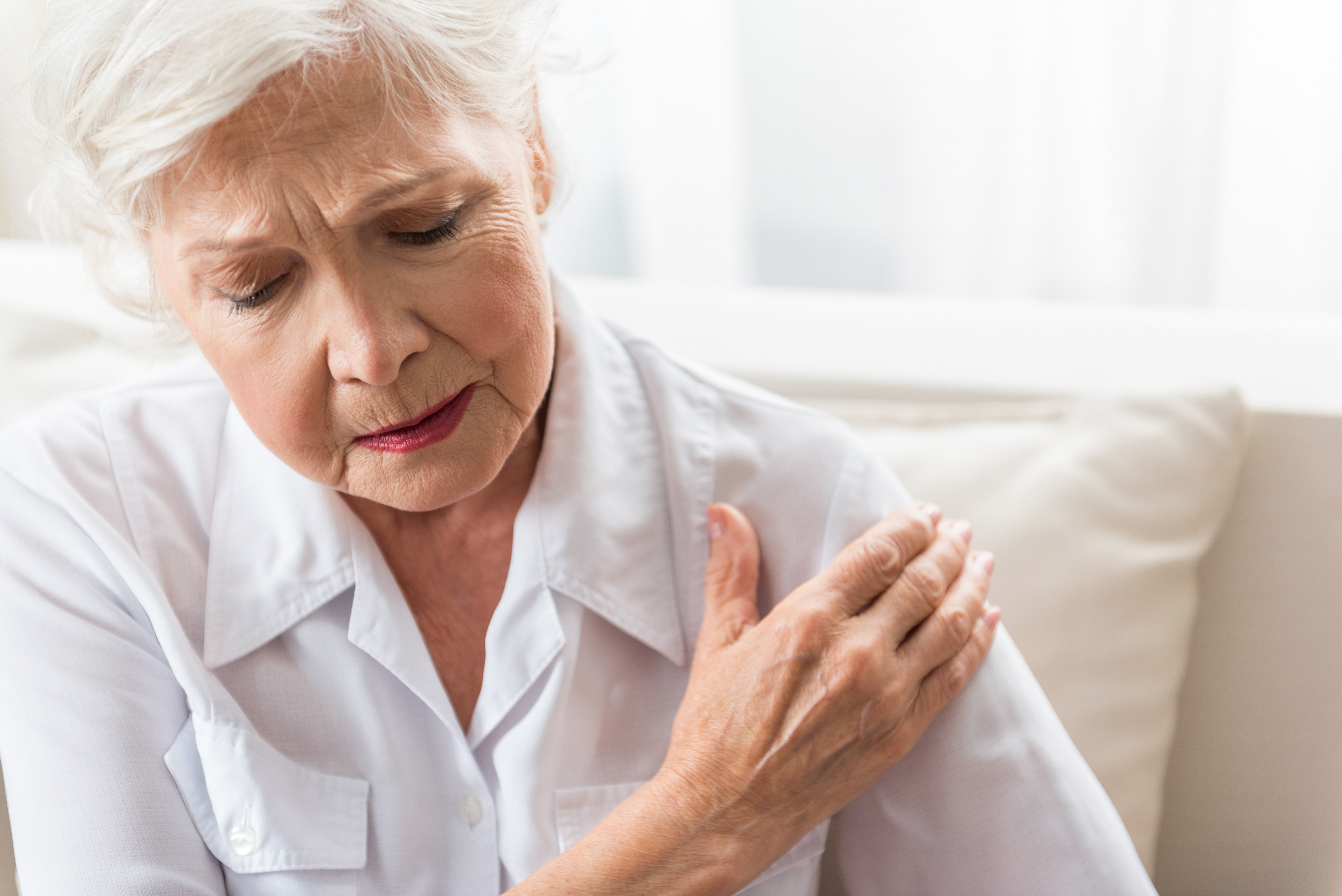 woman holding shoulder in pain