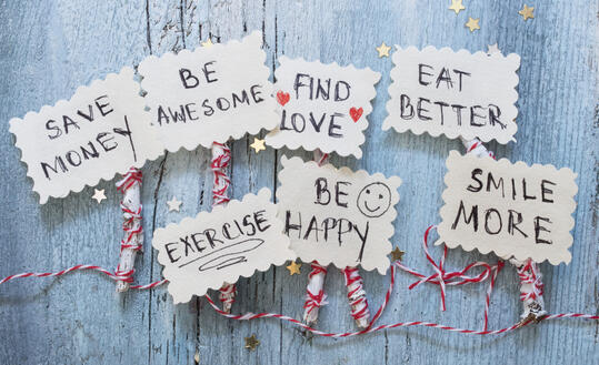 cutout photos on red and white twine saying resolutions like, save money, smile, be awesome, eat better, exercise, be happy, find love