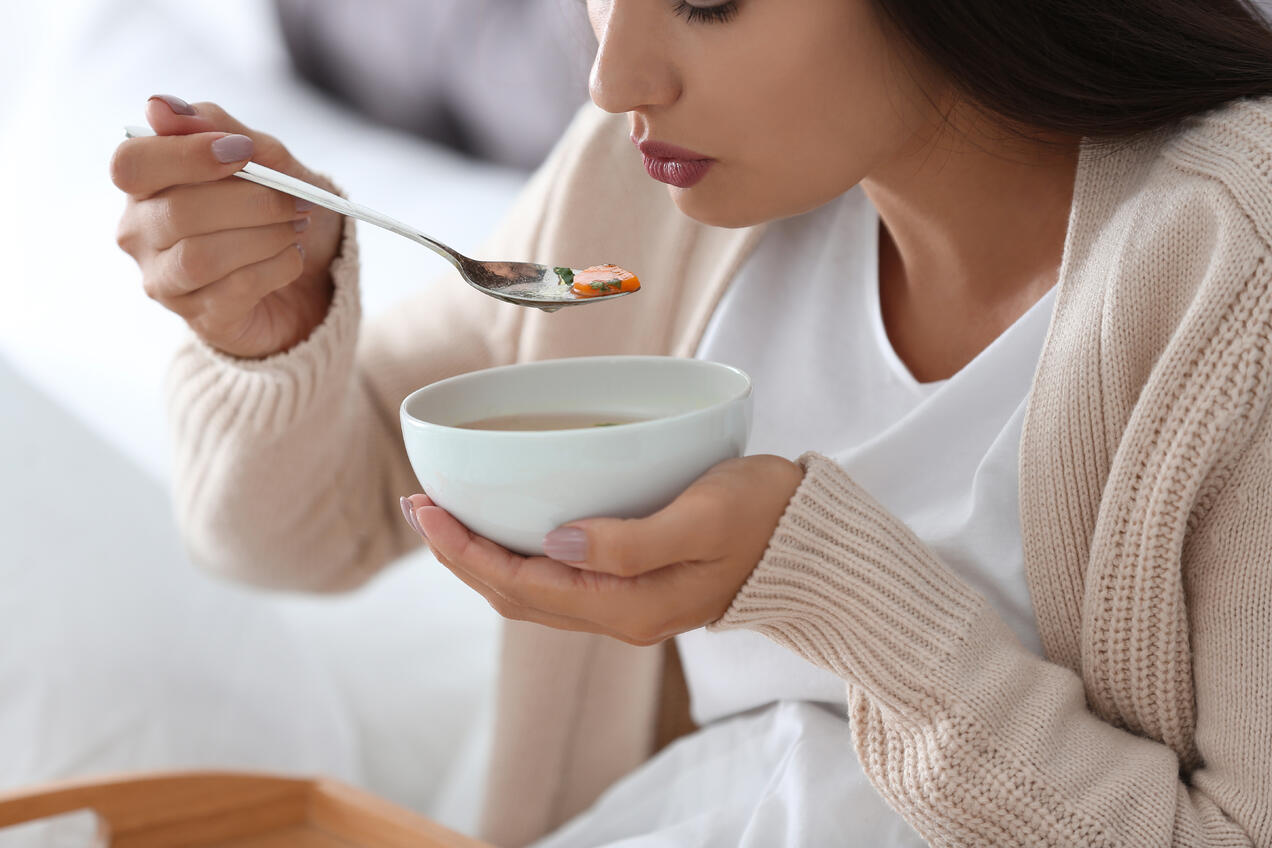 Sick woman eating soup