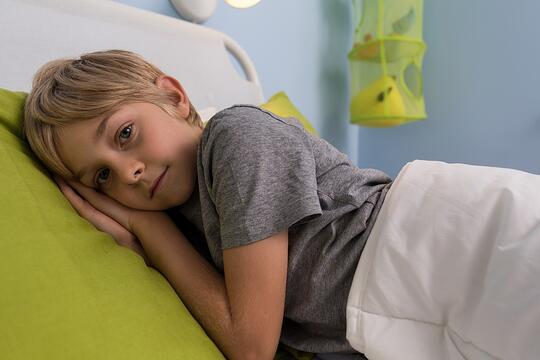 Portrait of ill child lying in hospital bed