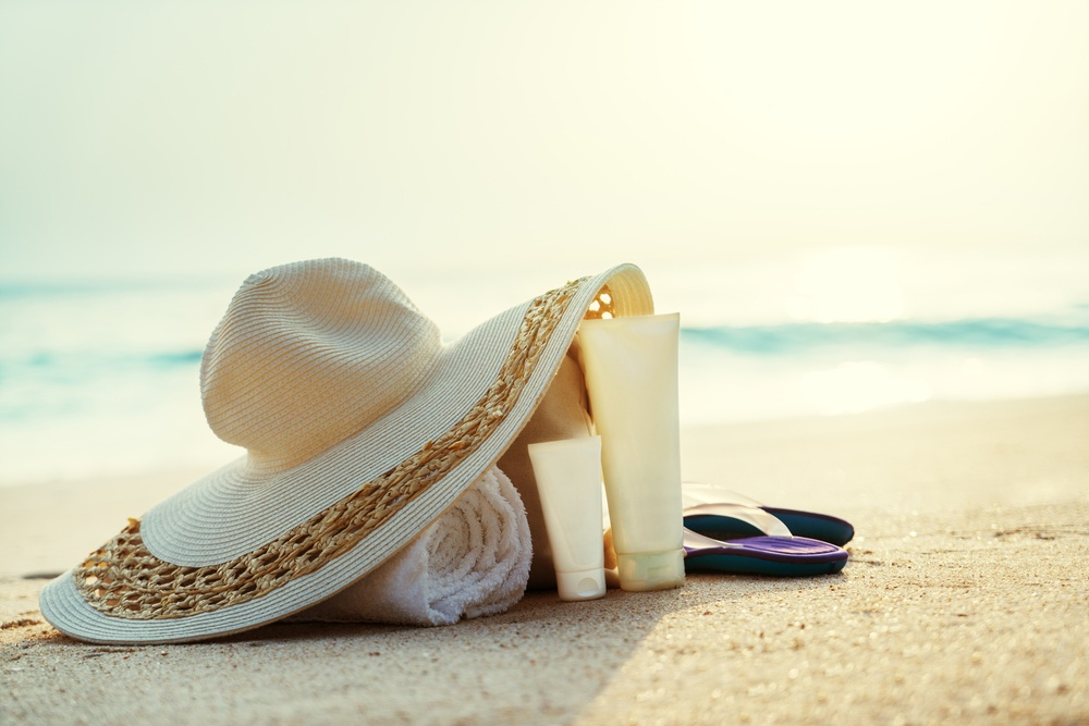 Sun lotion, hat  with bag at the beach