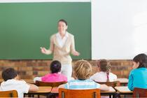 Pupils listening to their teacher at chalkboard at the elementary school.jpeg