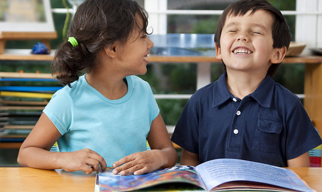 two preschool kids reading together