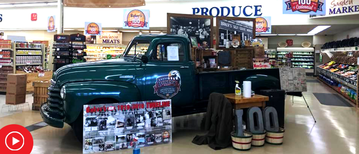 antique car display with 100 numbers celebrating store