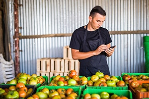 Guy checking his phone in front of his produce crates