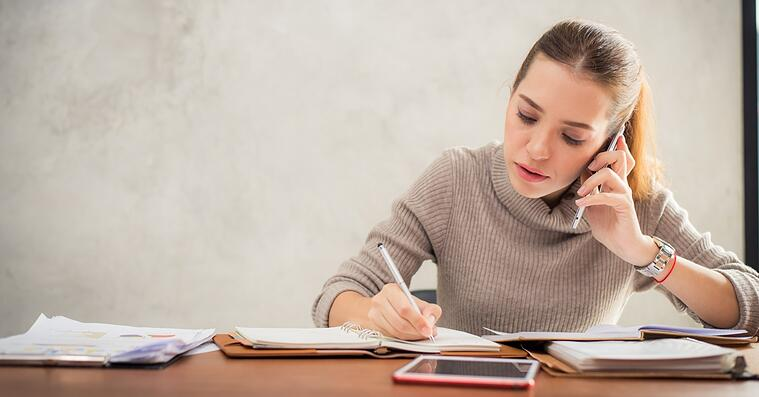 Mujer hablando por teléfono y tomando notas