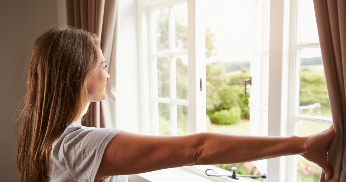 Mujer abriendo ventanas por monóxido de carbono
