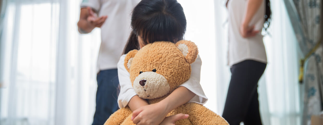 child hugs teddy bear while parents argue