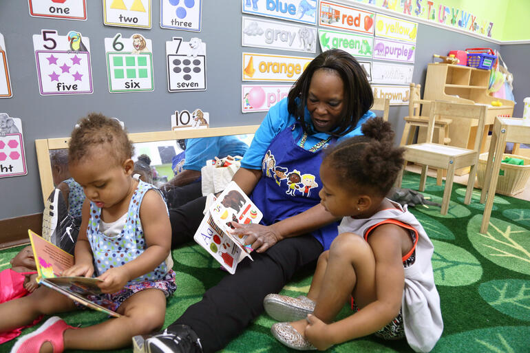 a teacher reads to two young learners