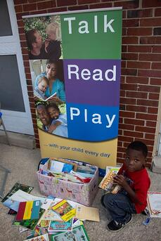A child sits next to Talk, Read, Play collection box.