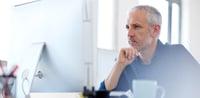 Man at a desk looking at a computer