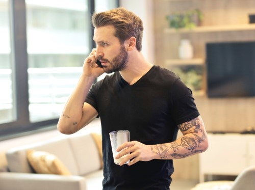 Man with tatoos talking on the phone
