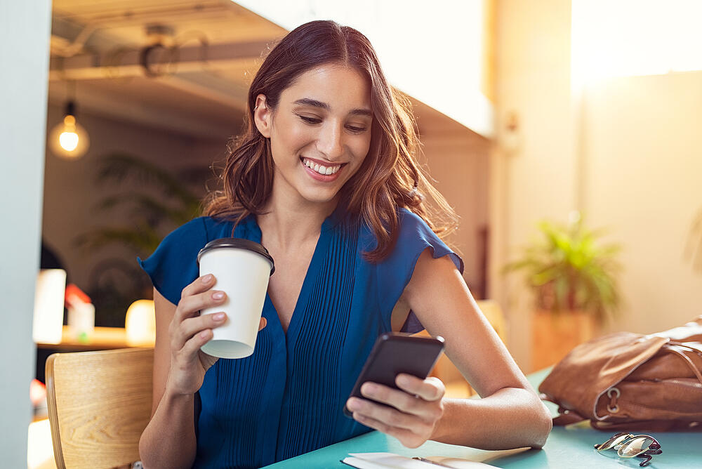Woman drinking coffee and looking at her checking account on her phone.