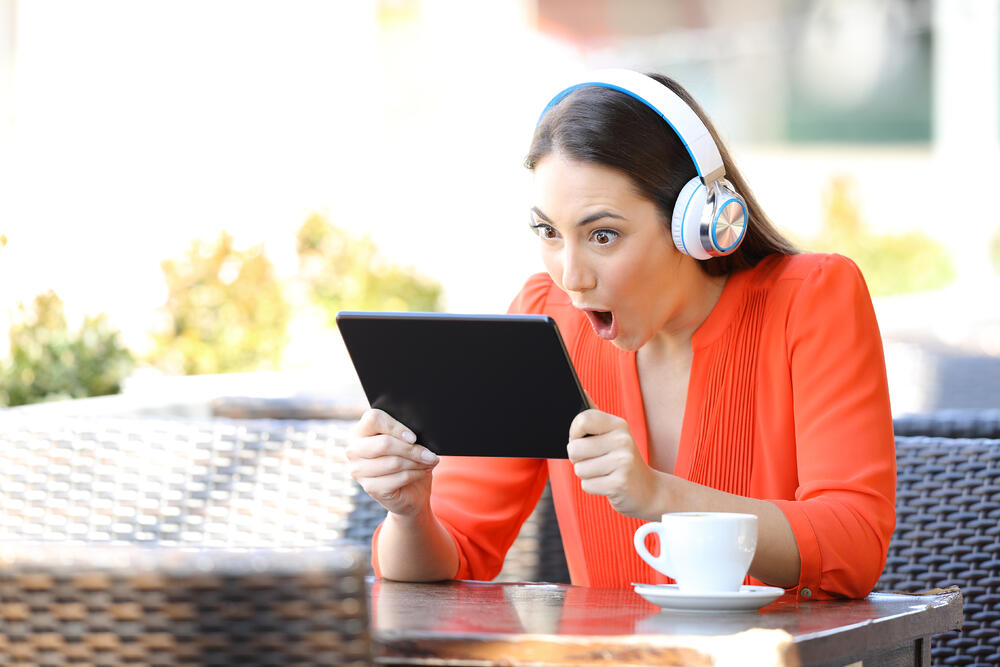 excited woman using tablet for discounts