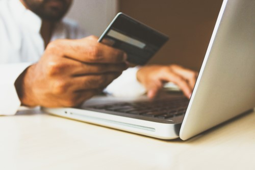 Person holding a blurred credit card using a laptop