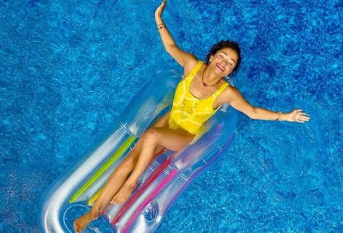 Woman in yellow bathing suit floating in a pool-1