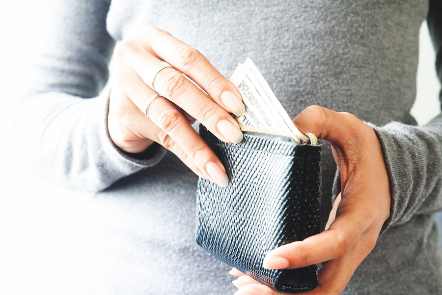 Woman putting money into her wallet from 52-week savings