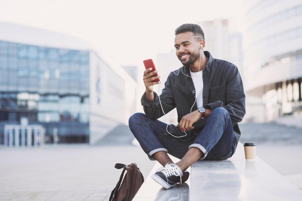 man looking at phone getting ACU Card alerts