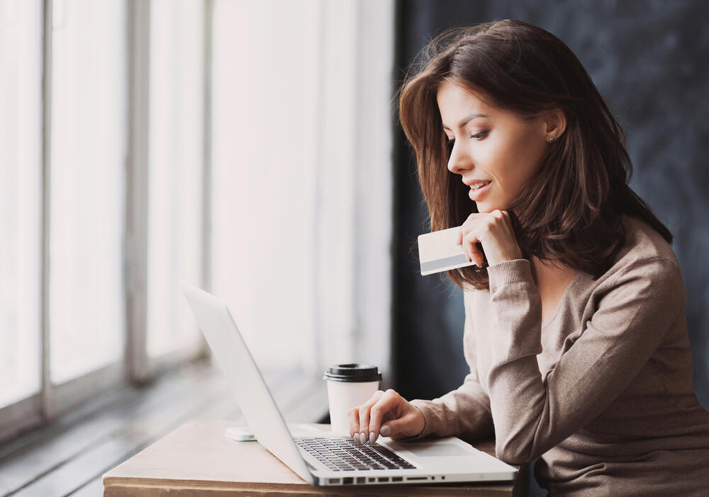 Woman looking at computer and holding credit card