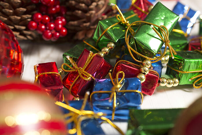 Selection of vibrant Christmas decorations on a light wooden surface