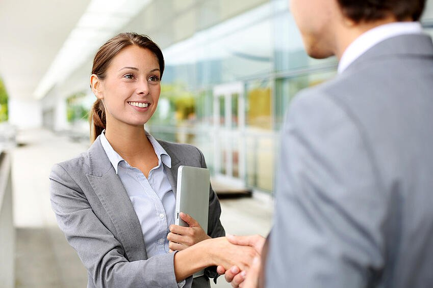 Businesswoman shaking hand to partner