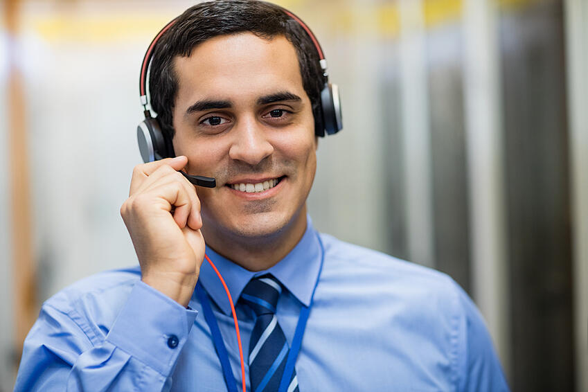 Portrait of happy technician talking on head phones
