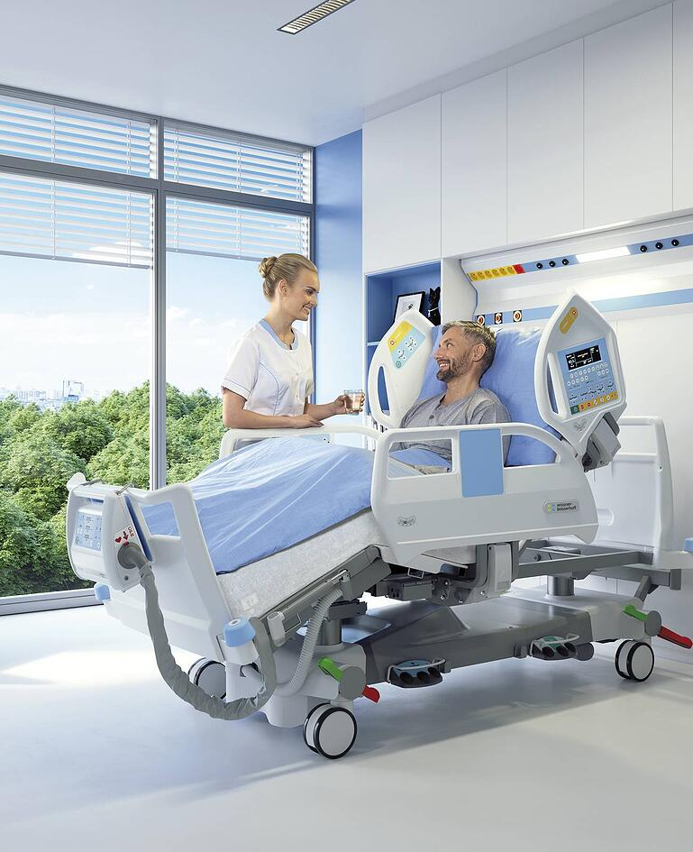 Mann in hochfunktionalem Intensivbett mit Luftschlauch am Fussende. Betreuerin reicht Mann ein Glas Wasser