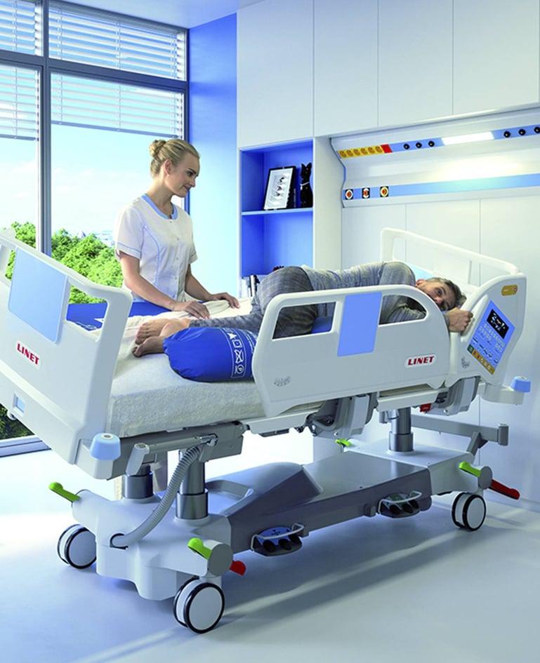 Mann in lateral geschwenktem Intensivbett, hält sich an Seitensicherung fest. Betreuerin wechselt Matratzenbezug