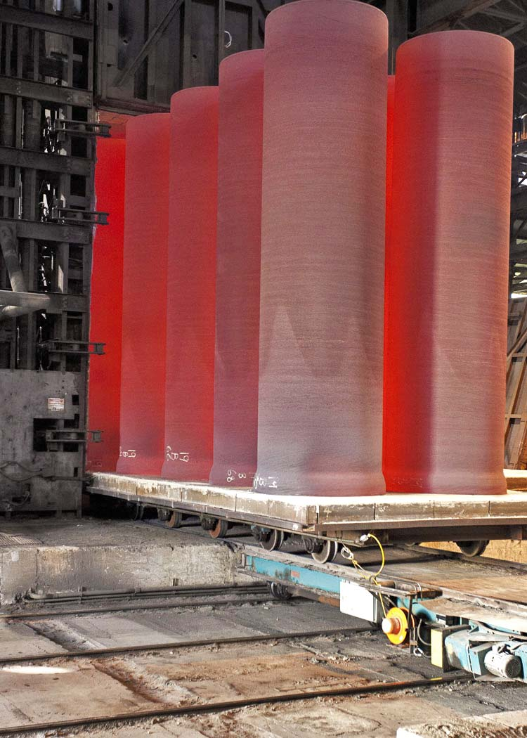 Ductile Iron Pipe being produced at a steel foundry. They are red hot due to their extreme temperature.