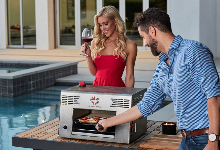 Man and wife cooking pizza in the Blazing Bull Portable Infrared Grill