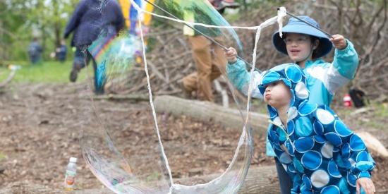 Image of two girls blowing a bubble in the park