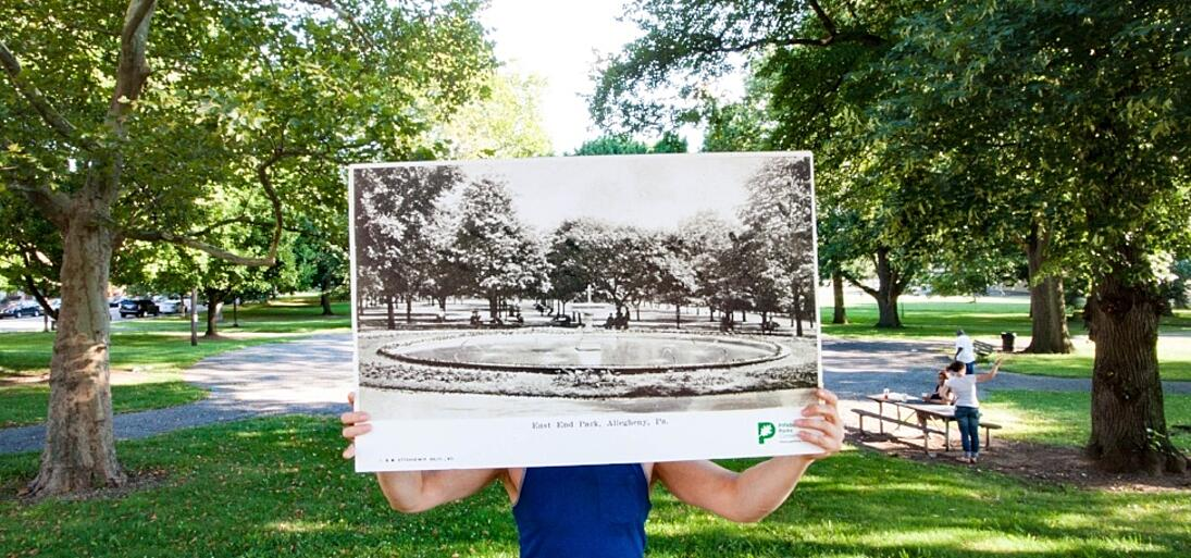 Image of a person holding up an old photo of Allegheny Commons in the park