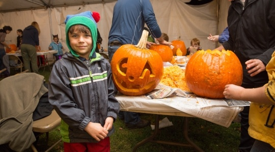 Image of a boy next to a jack-o-lantern