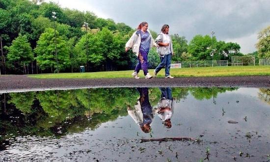 Image of two women walking near a flooded ballfield