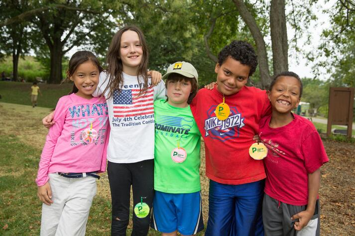 summer_camp_education_program_2015_mark_simpson_diverse_ethnic_line_kids_smile__outside_trees_pink_green_red_H