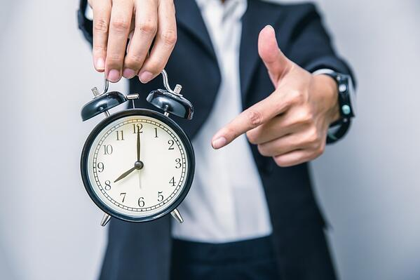 Man with clock showing urgency