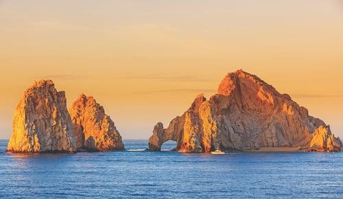 Los Cabos islands at sea orange sunset