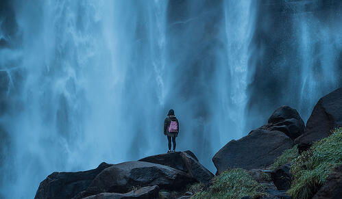 Person standing in front of waterfall