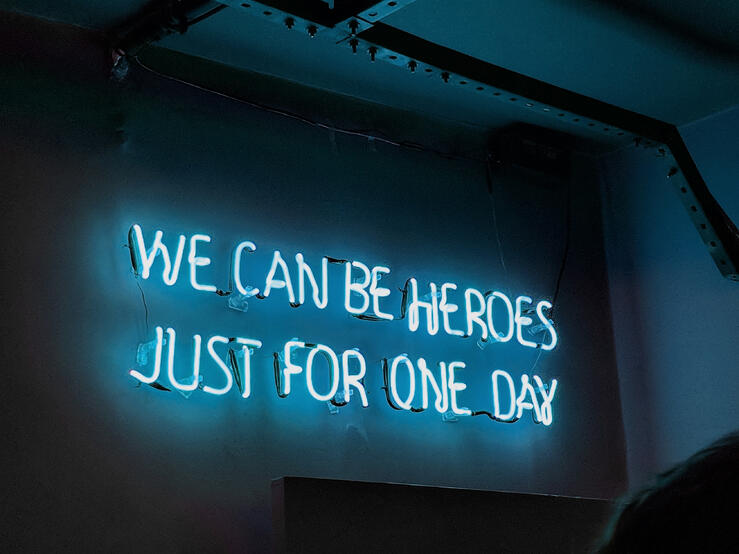 """Neon side that reads, """"We can be heroes just for one day."""""""