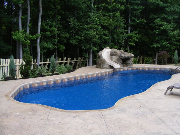 inground pool patio ideas white colonial home with grey patio and trees surrounding pool deckpatio drainage - Inground Pool Patio Designs