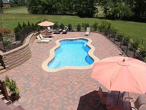 freeform pool and concrete paver patio with oversized umbrellas and lounge chairs