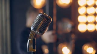 videoblocks-retro-microphone-on-stage-close-up-of-vintage-radio-microphone-silver-microphone-in-retro-style-old-microphone-on-stage-against-background-of-stage-lighting_hdfo1zugb_thumbnail-small01