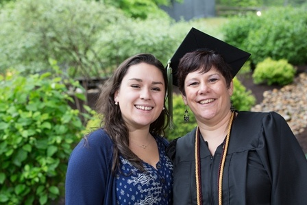 Mother graduates, supported by her daughter