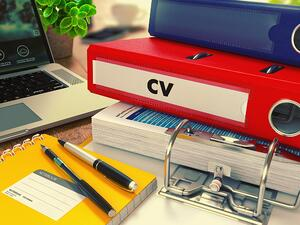 Red Office Folder with Inscription CV - Curriculum Vitae - on Office Desktop with Office Supplies and Modern Laptop. Business Concept on Blurred Background. Toned Image.