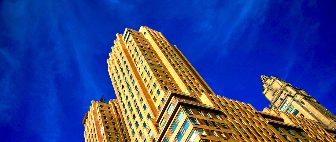 yellow skyscraper building against blue sky