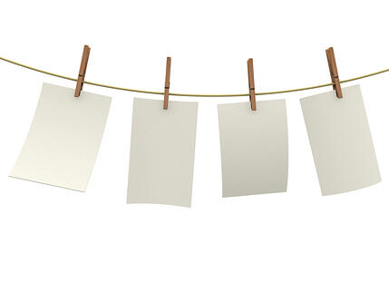 Clothes pin holding sheets of paper isolated over a white background