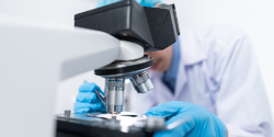 medical researcher looking in microscope